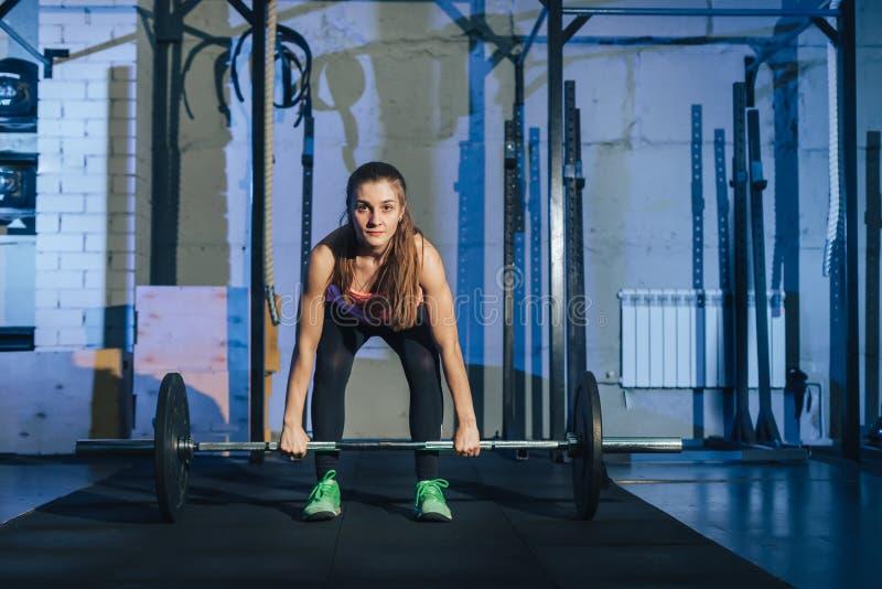 Muskulös ung konditionkvinna som lyfter en viktcrossfit i idrottshallen Skivstång för konditionkvinnadeadlift Crossfit kvinna royaltyfria foton