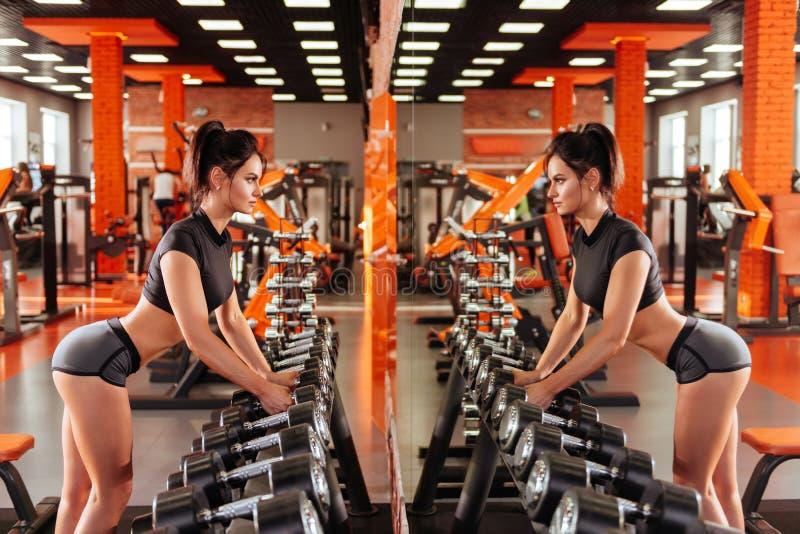 Muskulös ung kvinna med den härliga kroppen som gör övningar med hanteln arkivfoton
