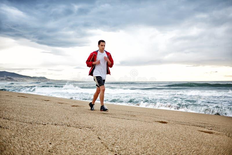 Muskulös ung man i ljus sportswearspring på stranden längs havet, HDR effekt royaltyfria foton