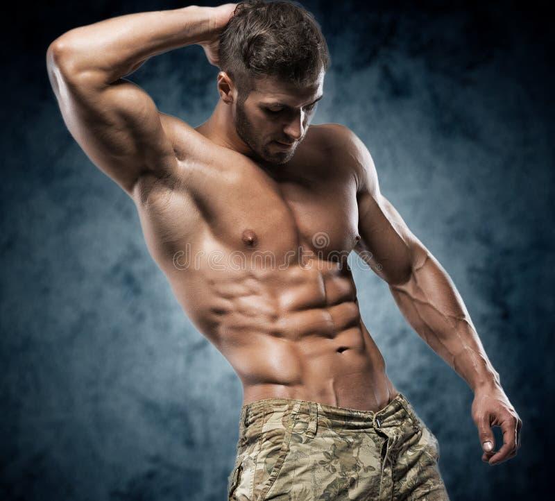 Muskulös ung man i studio på mörk bakgrund royaltyfria foton