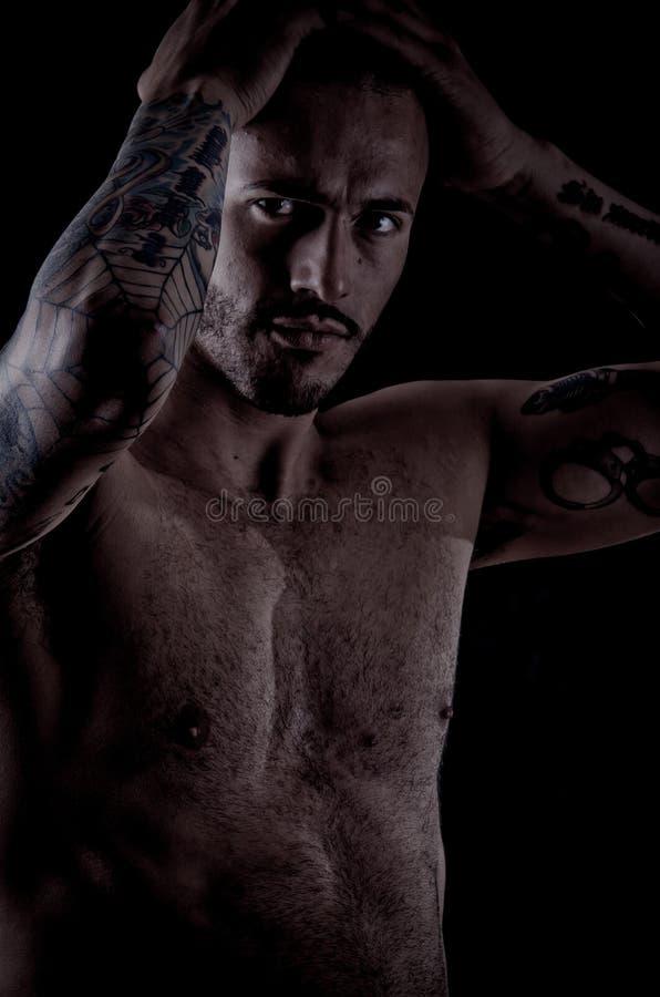 Muskulös ung man med många tatueringar, dragan stil fotografering för bildbyråer