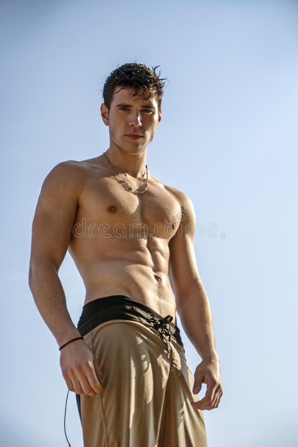 Muskulös ung man som är shirtless mot himlen arkivbilder