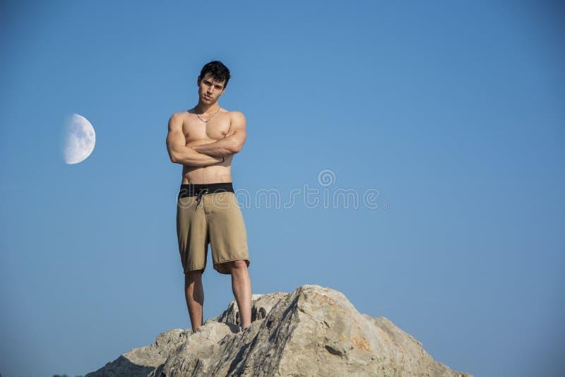 Muskulös ung man som är shirtless mot himlen med arkivbilder