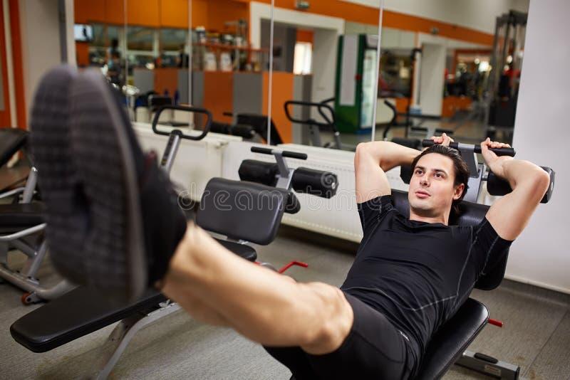 Muskulös ung sportig man i den svarta sportwearen som gör push-UPS med hans ben i idrottshallen arkivbild