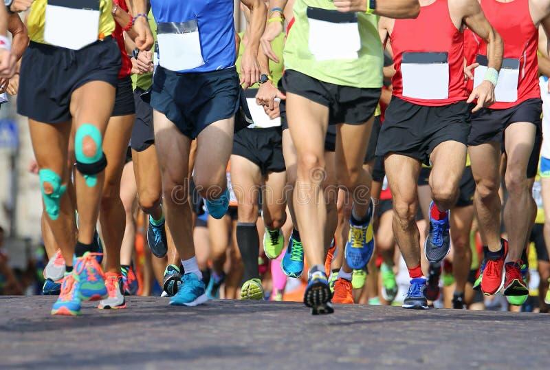 muskulösa ben av ett stort antal löpare under sportar springer arkivfoto