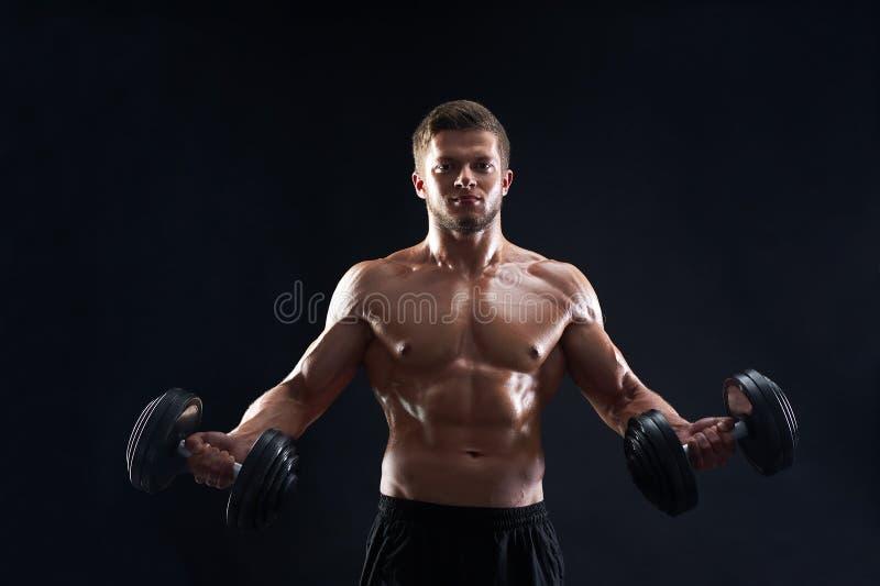 Muskulösa lyftande vikter för ung man på svart bakgrund royaltyfria foton