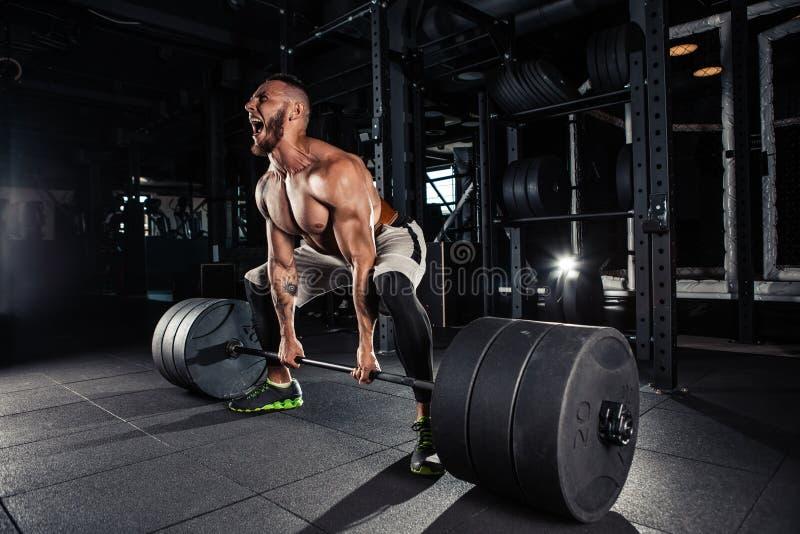 Muskulösa män som lyfter Deadlift arkivfoto