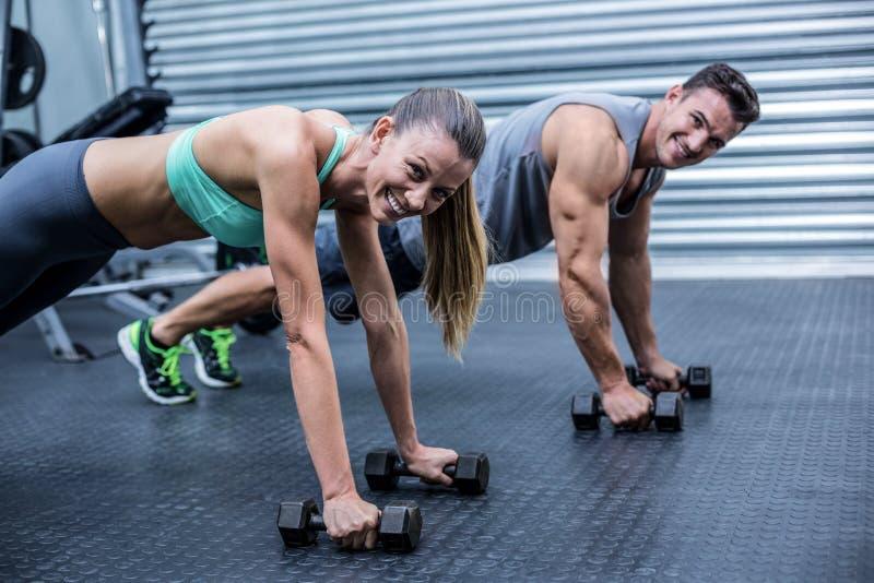 Muskulösa par som gör plankan, övar tillsammans arkivfoto