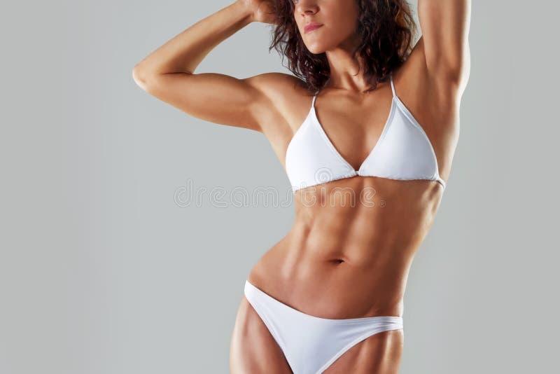 Muskulöse athletische junge Frau in einem weißen Badeanzug Eignung stockfotografie