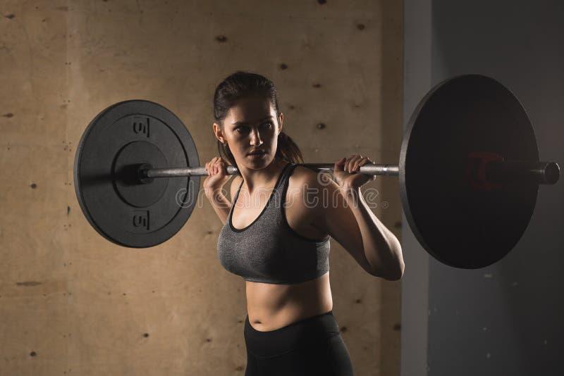 Muskulöse Frau in einer Turnhalle, die Schwergewichts- Übungen mit Barbell tut lizenzfreie stockfotos