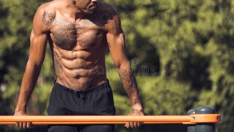 Muskulöse Guy Doing Street Workout On-Stangen im Park stockbild