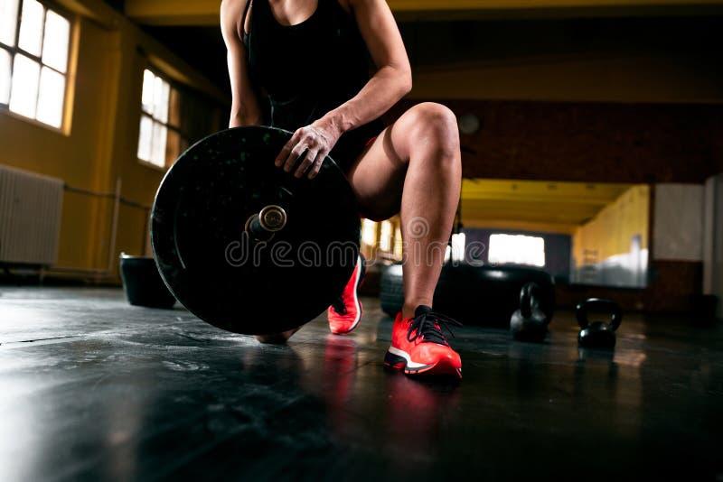 Muskulöse junge Frau, die schwere Gewichte für Übung setzt stockbild