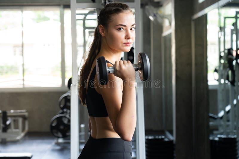 Muskulöse junge Frau mit dem schönen Körper, der Übungen mit d tut stockfotos