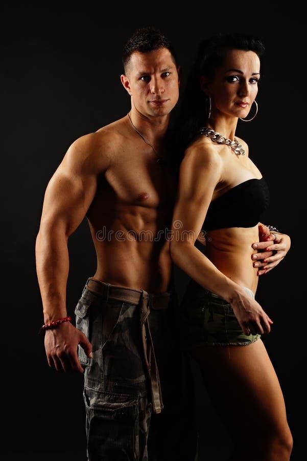 Muskulöse Mannhaltungen mit seinem Mädchen lizenzfreie stockfotografie