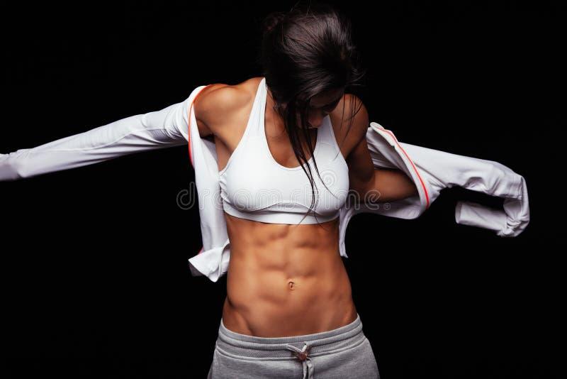 Muskulöse tragende Sportjacke der jungen Frau stockbilder