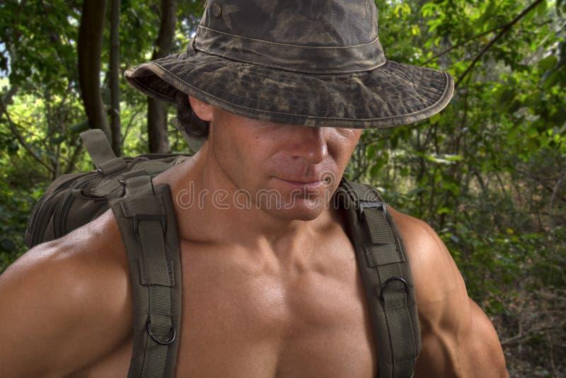 Muskulöser Abenteuermann in camo Hut, der im Dschungel wandert lizenzfreie stockbilder