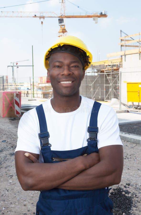Muskulöser Afroamerikanerbauarbeiter an der Baustelle lizenzfreie stockbilder