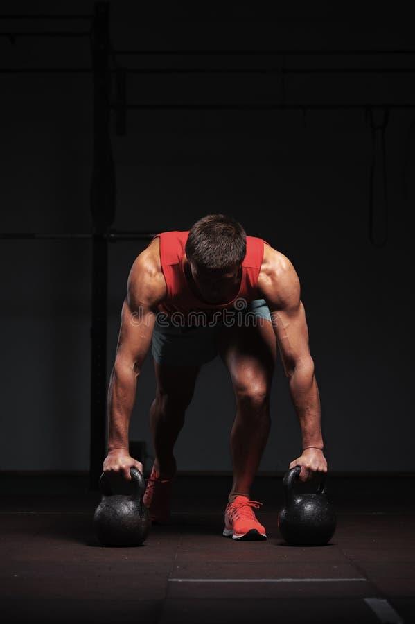 Muskulöser athletischer Mann, der in der Turnhalle trainiert lizenzfreie stockfotos