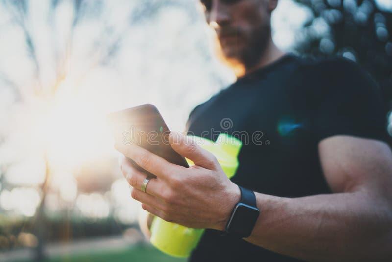 Muskulöser bärtiger Athlet, der gebrannte Kalorien auf Smartphoneanwendung nach Sitzung des guten Trainings im Freien auf Stadt ü stockfotografie