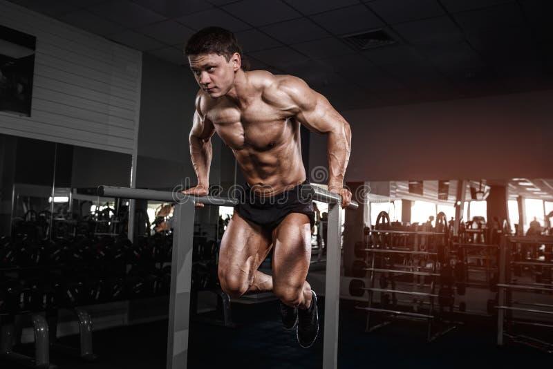 Muskulöser Bodybuilder, der in der Turnhalle tut Übungen auf paral ausarbeitet lizenzfreie stockfotos
