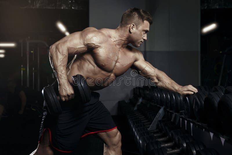 Muskulöser Bodybuilderkerl, der Übungen mit Dummkopf in der Turnhalle tut stockfoto