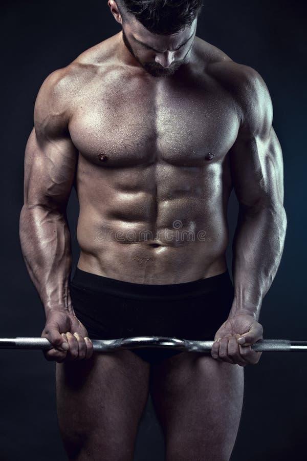 Muskulöser Bodybuilderkerl, der Übungen mit großem Dummkopf tut stockfotografie