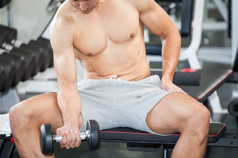 Muskulöser Bodybuilderkerl, der die Übungen sitzen mit Gewicht lif tut stockfotografie