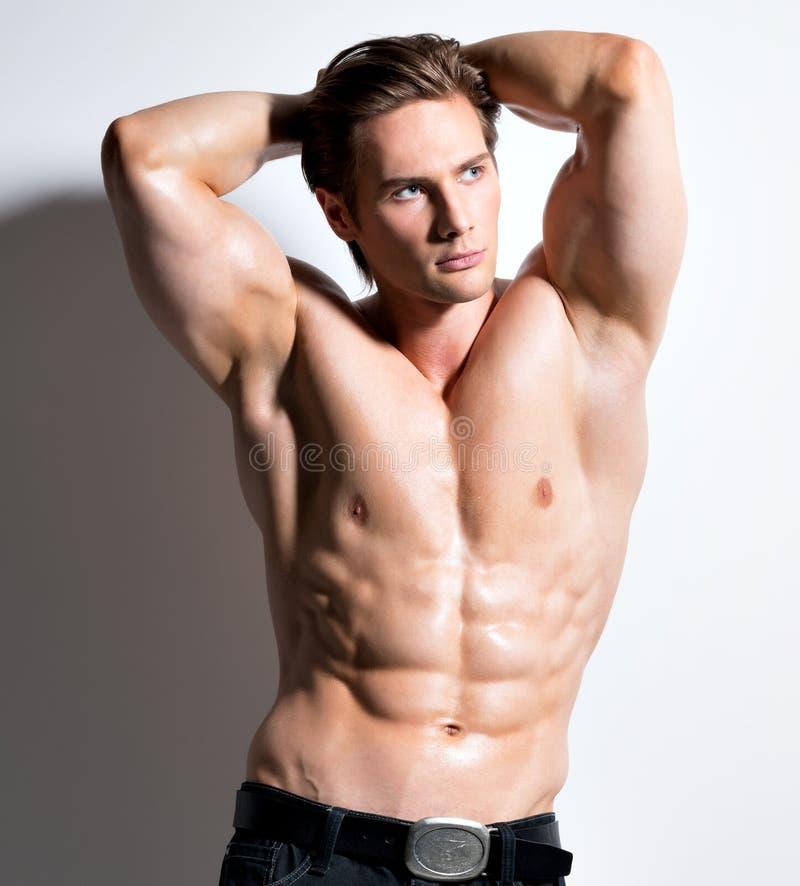 Muskulöser gutaussehender Mann mit den Händen hinter Kopf. lizenzfreie stockfotos
