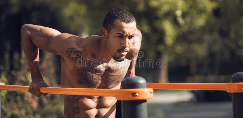 Muskulöser Guy Doing Street Workout, trainierend auf Barren stockbild