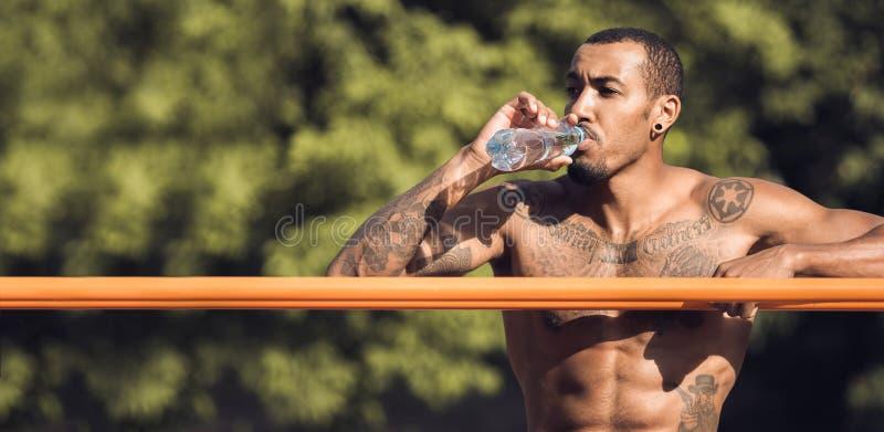 Muskulöser Guy Relaxing After Intense Workout, Trinkwasser lizenzfreies stockbild