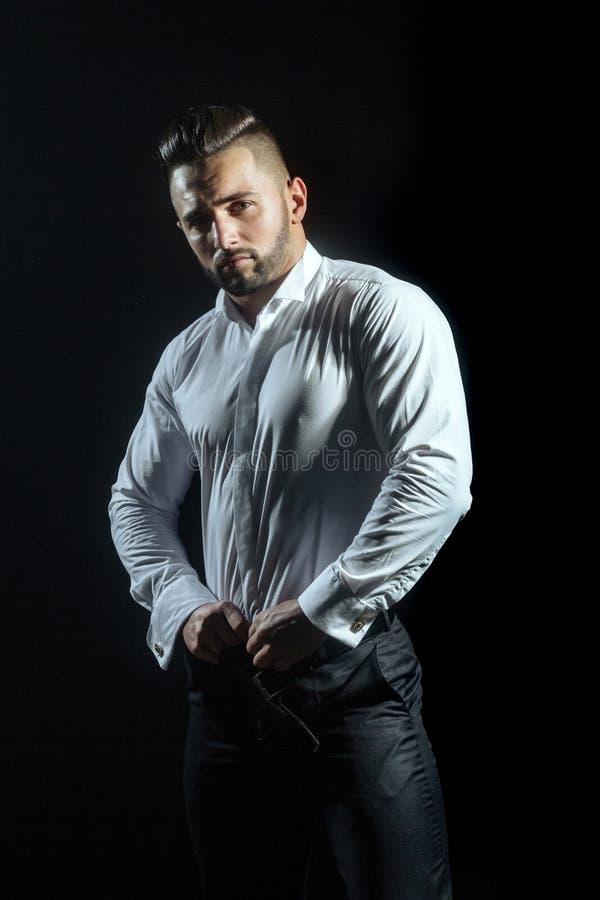 Muskulöser hübscher Kerl auf schwarzem Hintergrund wirft tragendes elegantes weißes Hemd und schwarze Hose auf Kleiderordnung für lizenzfreies stockfoto