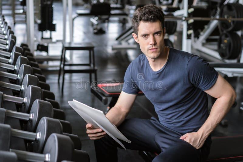 Muskulöser hübscher Trainer, der Eignungsplan auf Klemmbrett nach dem Ausarbeiten in der Eignungsturnhalle betrachtet lizenzfreie stockfotos