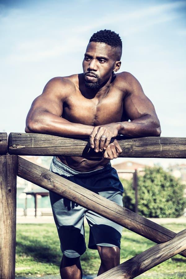 Muskulöser hemdloser schwarzer Mann im Park lizenzfreie stockfotografie