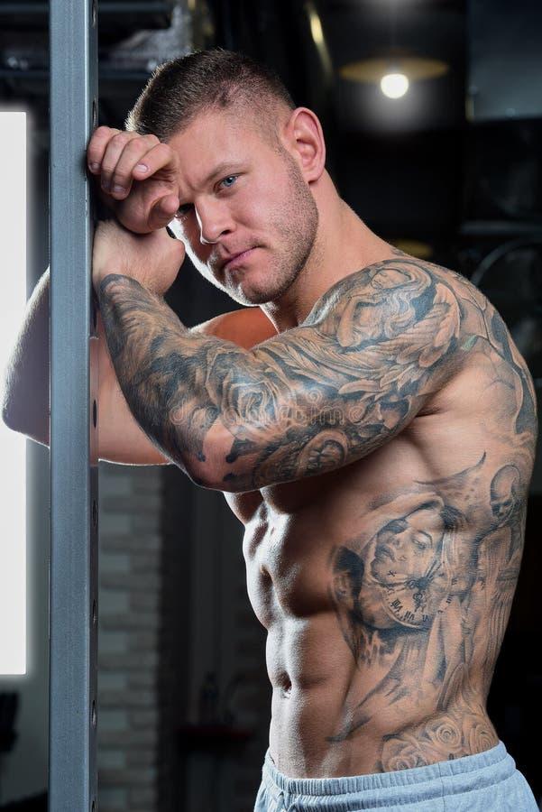 Muskulöser hemdloser zerrissener starker entspannter Mann mit blauen Augen und Tätowierung wirft auf einem Energiekäfig in den Ho lizenzfreie stockfotografie