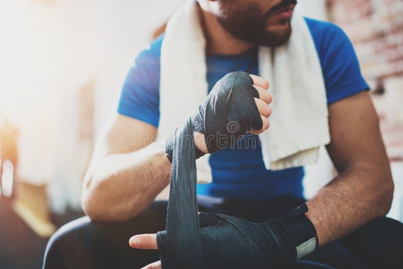 Muskulöser junger Boxer mit schwarzen Verpackenverbänden Fäuste des Kämpfers vor dem Kampf oder dem Training in der Sportturnhall lizenzfreies stockbild
