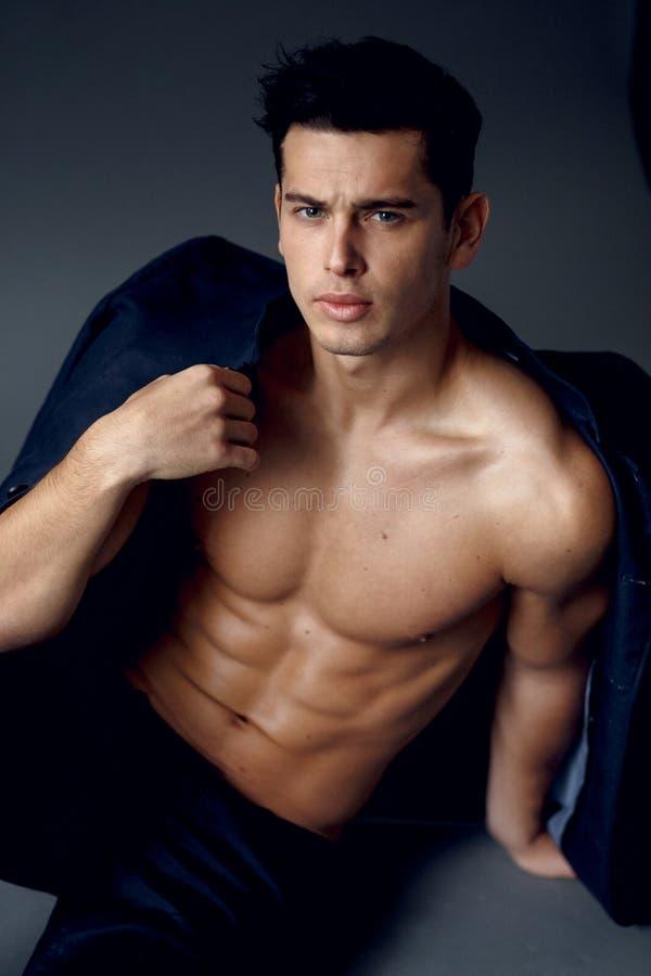 Muskul?ser, junger brunette Mann, der in der modernen Klage auf einem nackten Torso, auf grauem Hintergrund sitzt und aufwirft lizenzfreies stockbild