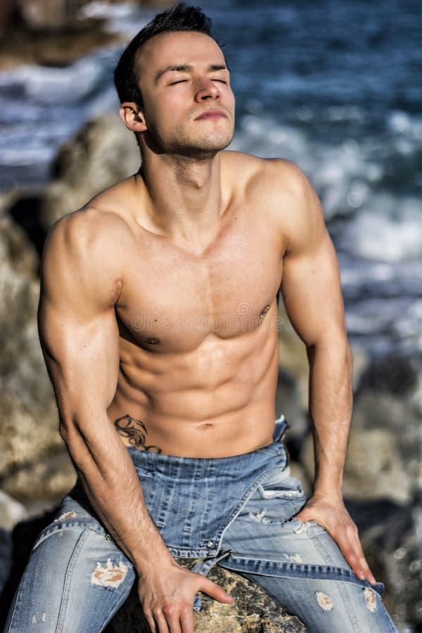 Muskulöser junger Mann, der auf Felsen durch Meer ein Sonnenbad nimmt lizenzfreie stockbilder
