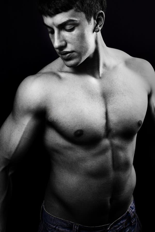 Muskulöser junger Mann in der Dunkelheit stockfotografie
