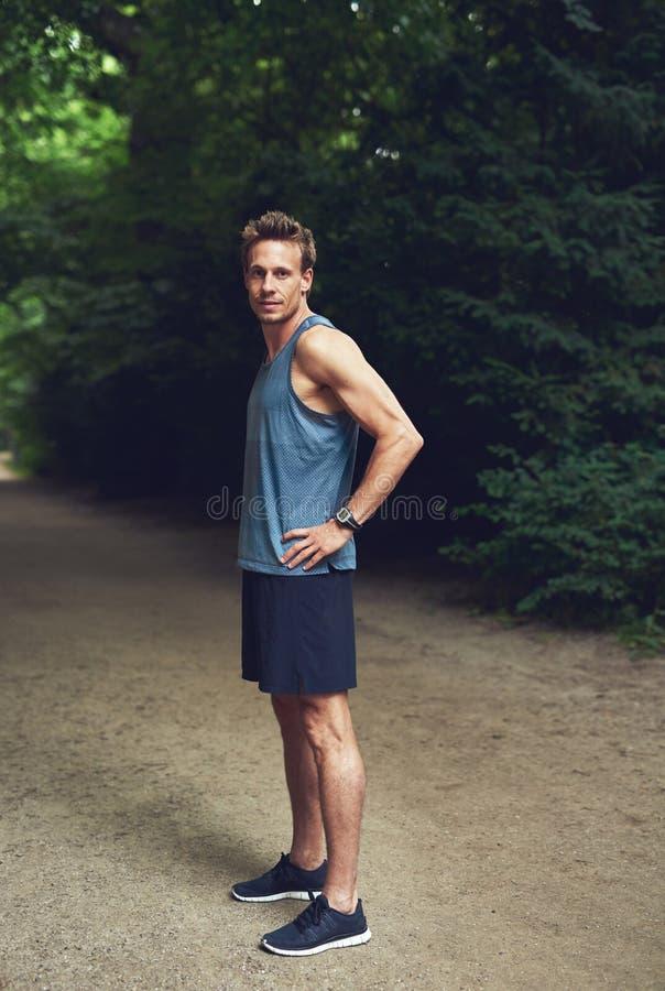 Muskulöser junger Mann, der am Park steht stockbilder