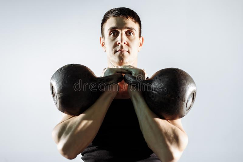 Muskulöser junger Mann, der Schwergewichts- Übung für Bizeps tut lizenzfreies stockfoto
