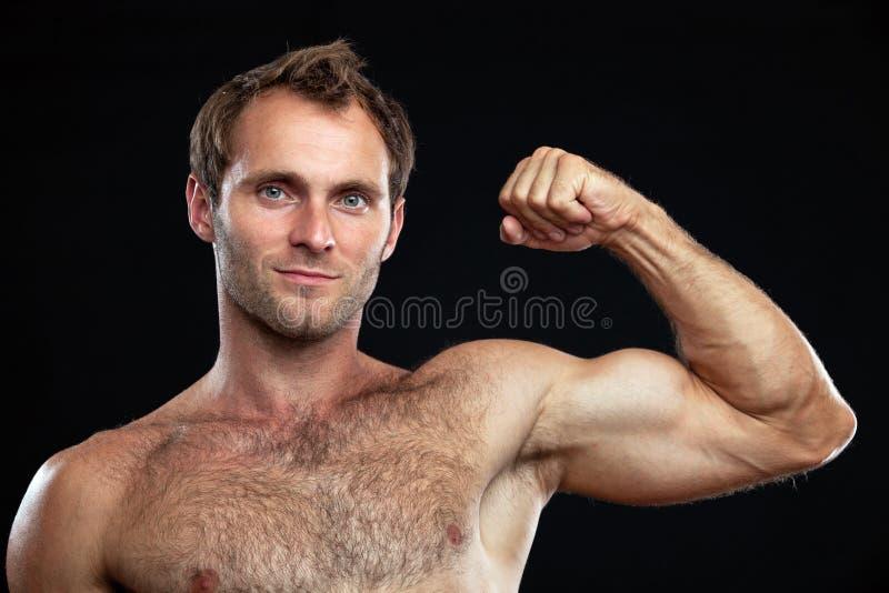 Muskulöser junger Mann, der sein bicep biegt stockfotos