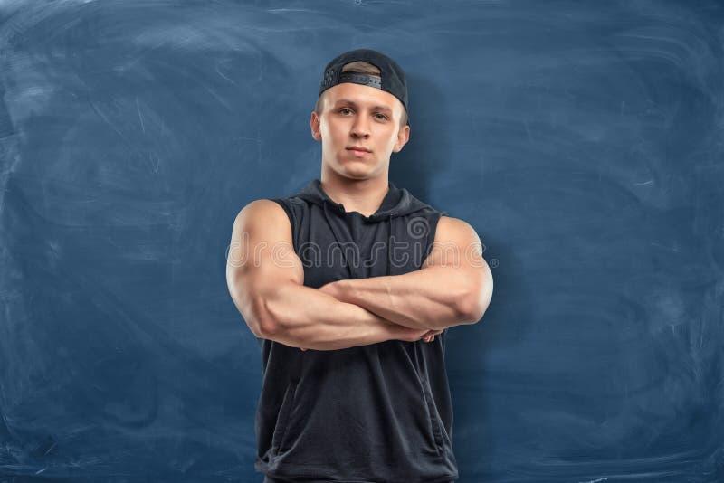 Muskulöser junger Mann in der Sportkleidung, die mit seinen Armen steht, faltete sich auf dem dunkelblauen Hintergrund lizenzfreie stockfotografie