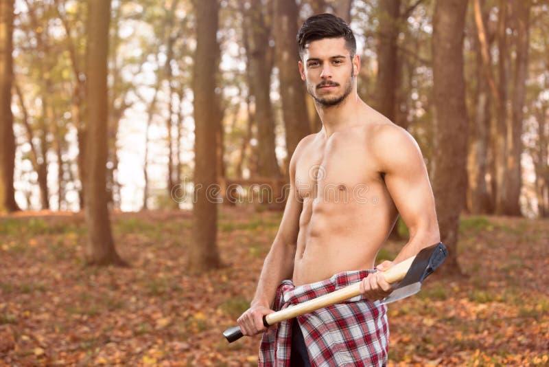 Muskulöser junger Mann mit Axt stockbild