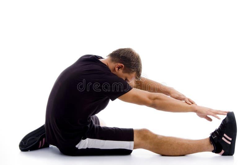 Muskulöser Kerl, der seine Fahrwerkbeine und Hände ausdehnt lizenzfreie stockfotos
