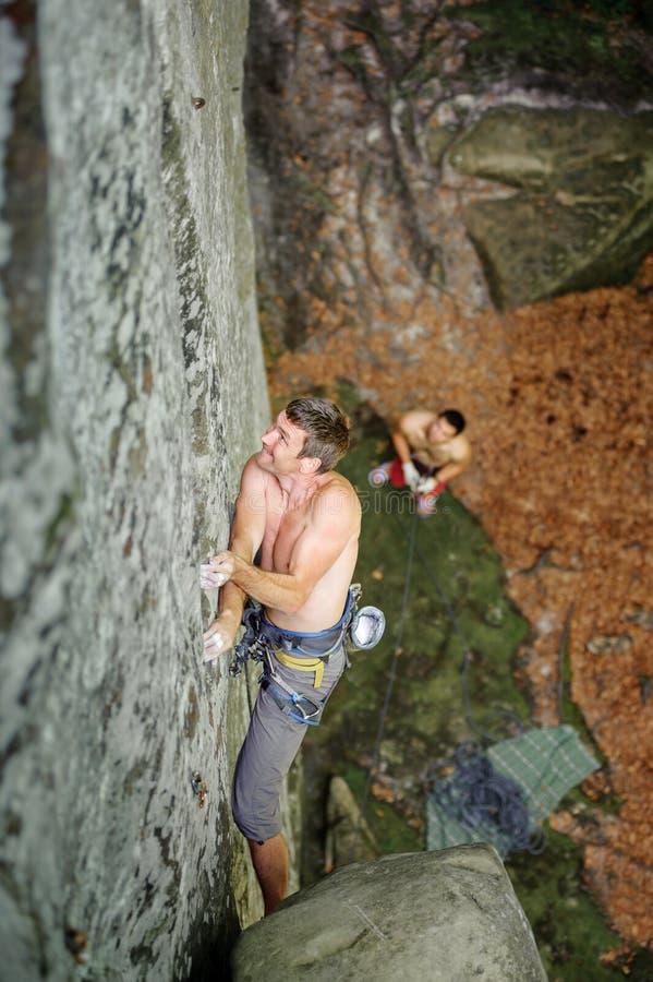 Muskulöser Kletterer klettert auf Klippenwand mit Seil stockfotografie