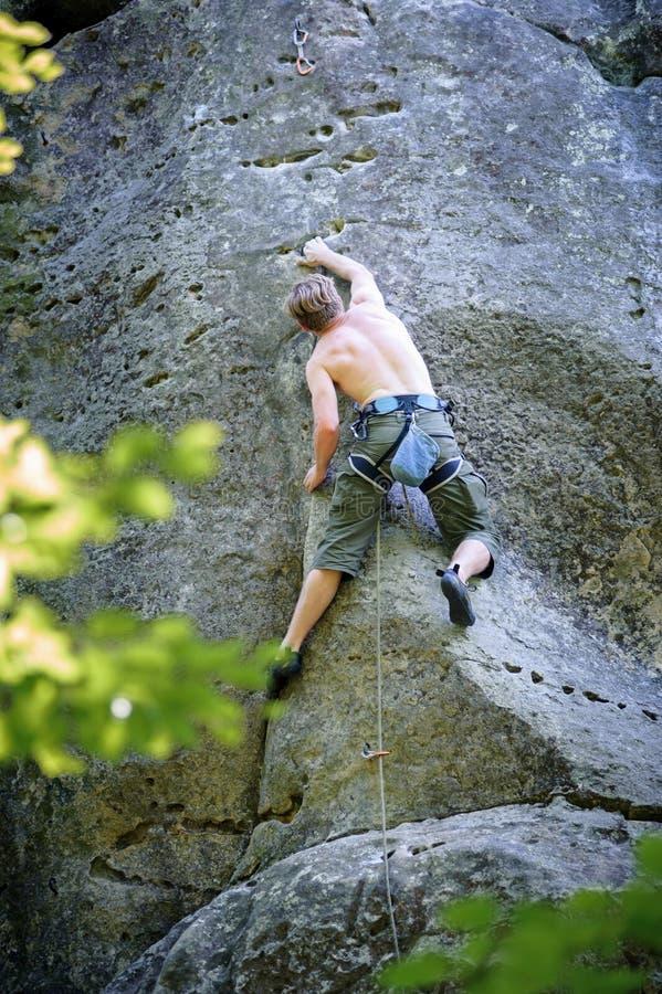 Muskulöser Kletterer klettert auf Klippenwand mit Seil stockfotos