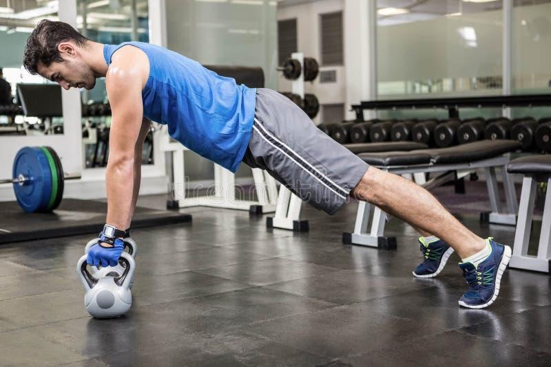 Muskulöser Mann, den das Handeln drückt, ups mit kettlebells stockbild