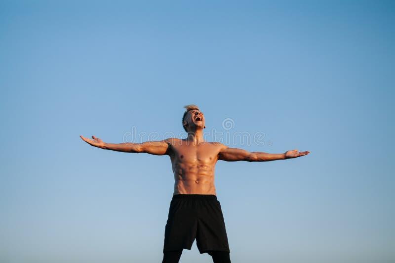 Muskulöser Mann, der auseinander mit den Händen schreit lizenzfreie stockfotos