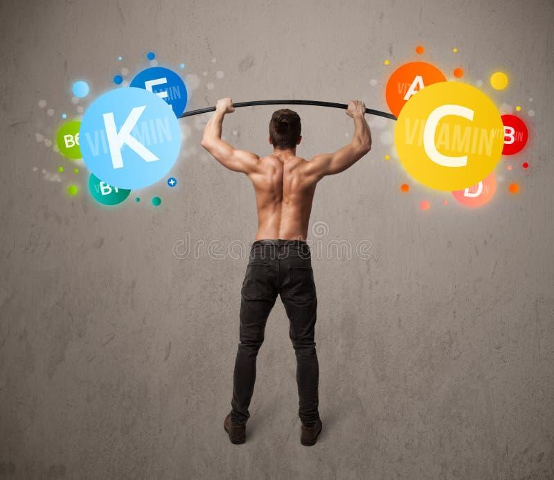 Muskulöser Mann, der bunte Vitamingewichte anhebt lizenzfreie stockbilder