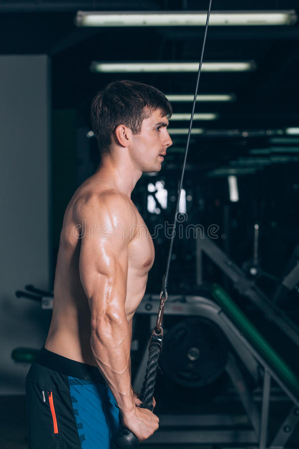 Muskulöser Mann, der in der Turnhalle tut Übungen am Trizeps, starke männliche nackte Torso-ABS ausarbeitet lizenzfreie stockbilder